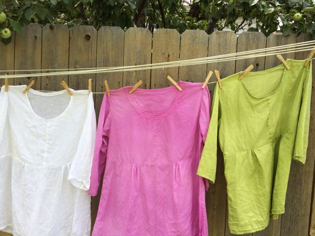 Three tunic tops on a clothesline. From left to right, they're white, pink, and green.