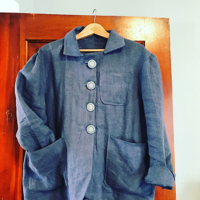 Blue linen jacket with three pockets, hanging on a door.